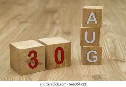 Cube shape calendar for AUGUST 30 on wooden surface.