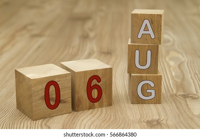 Cube shape calendar for AUGUST 6 on wooden surface.