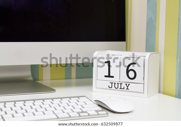 Cube shape calendar for JULY 16 and computer with white screen on table.