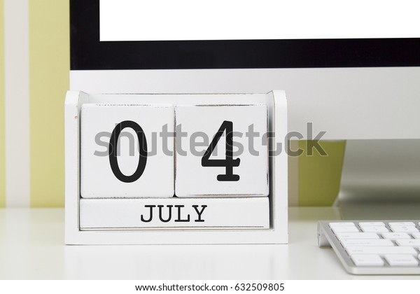 Cube shape calendar for JULY 4 and computer with white screen on table.