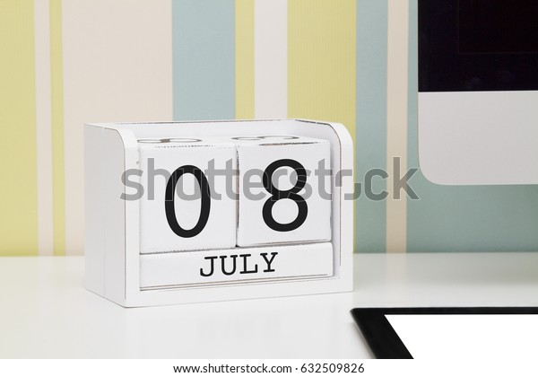Cube shape calendar for JULY 8 and computer with white screen on table.