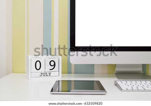 Cube shape calendar for JULY 9 and computer with white screen on table.