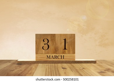 Cube shape calendar for March 31 on wooden surface with empty space for text.