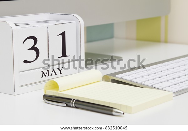 Cube shape calendar for MAY 31 and computer with white screen on table.