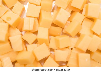 Cube sliced cheese on a plate. Meal ingredient.