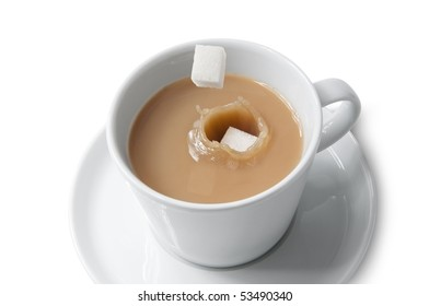 Cube sugar dropping into cup of tea with milk