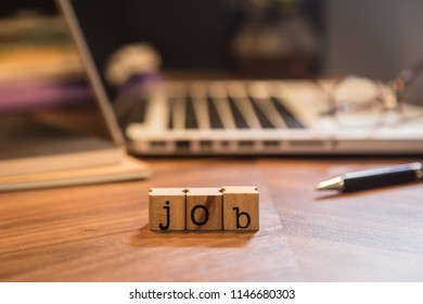 Cube wooden stamps with letters word Job on office table. Blur notebook, pen, glasses and books in background. Worldwide work at home, hiring, recruitment and human resources concepts.