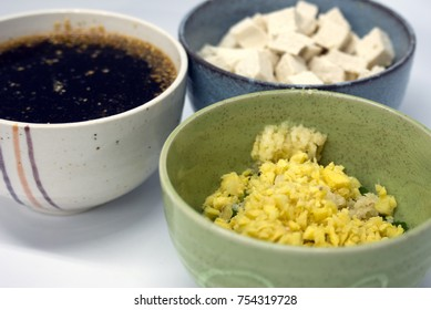 Cubed tofu, minced garlic and diced ginger, and a tamari-based sauce in three separate ceramic rice bowls