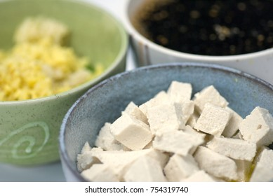 Cubed tofu, minced garlic and diced ginger and a tamari-based sauce in three separate ceramic rice bowls