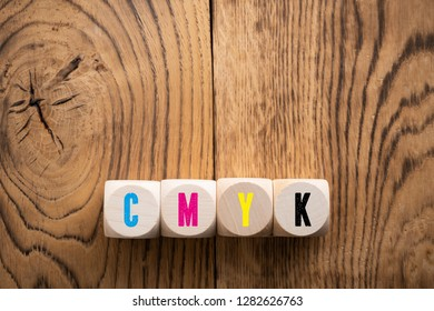 cubes with colored letters for CMYK on wooden background