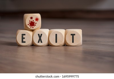 Cubes and dice with corona virus icons and exit strategy on wooden background