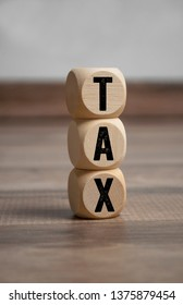 Cubes and dice with tax on wooden background