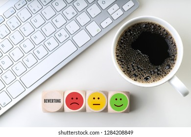 """cubes with emoticons, ther German word for """"rating"""", a computer keyboard and coffee"""