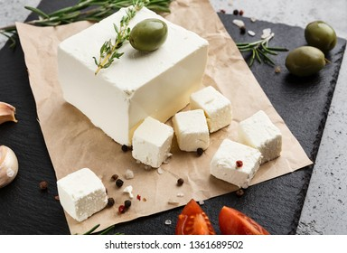 Cubes of feta cheese with olive and rosemary on craft paper over concrete background. Homemade greek cheese concept