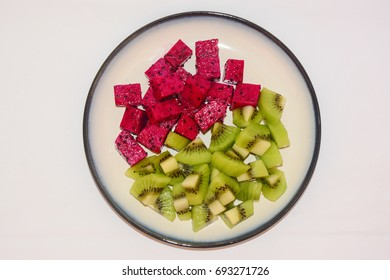 Cubes of fresh Red Dragon fruit and Kiwi fruit on a white ceramic plate with blue outline.  White background.