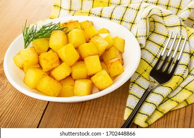 Cubes of fried potatoes, dill in white plate, fork on checkered napkin on wooden table