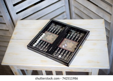 Cubes and game pieces on a backgammon board, on wooden table.