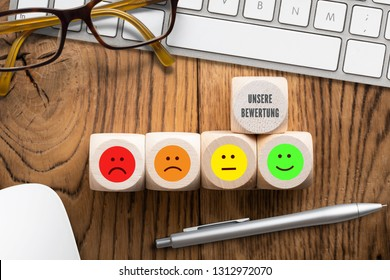 "cubes with the German phrase for ""Our rating"" and emoticons in front of a computer keyboard on wooden background"