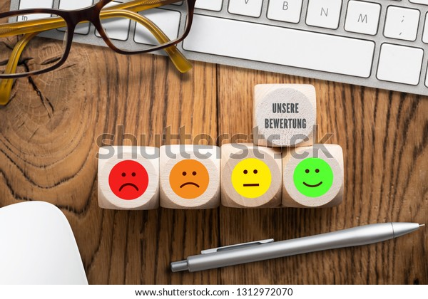 """cubes with the German phrase for """"Our rating"""" and emoticons in front of a computer keyboard on wooden background"""