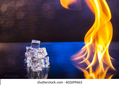 cubes of ice and fire on a water surface on an abstract blue background.
