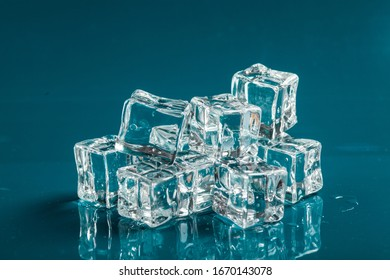 Cubes of ice on blue background with water drops