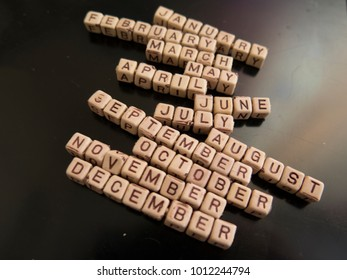 Cubes with letters constituting the names of the months on a black background