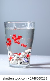 cubes with letters and numbers are submerged in water, letters and numbers are drowned in a glass of water