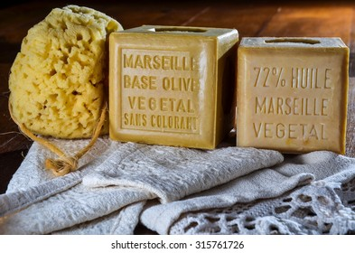 cubes of marseilles natural soap with yellow sponge and white cotton bath towel
