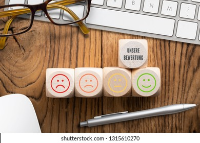 "cubes with message ""our ranking"" in German, emoticons on cubes and computer keyboard on wooden background"