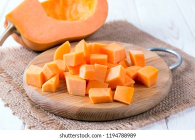 Cubes of pumpkin on cutting board on wooden table