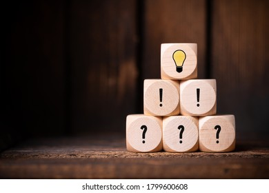 cubes with question marks, exclamation marks and a lightbulb symbol in front of wooden background