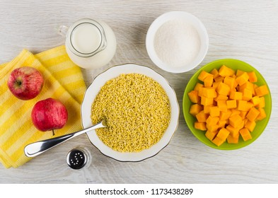 Cubes of raw pumpkin in bowl, apples on napkin, bowl with millet, jug of milk, sugar, salt on wooden table. Top view