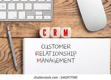 "cubes showing the acronym ""CRM"" and the explanation ""customer relationship management"" on wooden background"