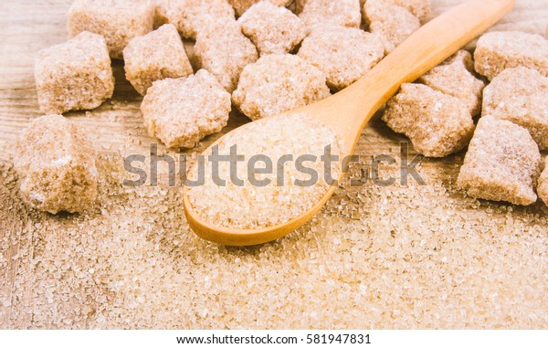Cubes of sugar - brown sugar cane on the wooden background.