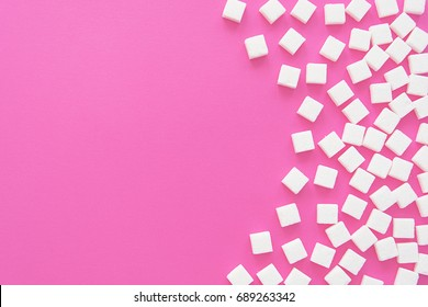 Cubes of sugar on a pink background. Empty space for copying text.