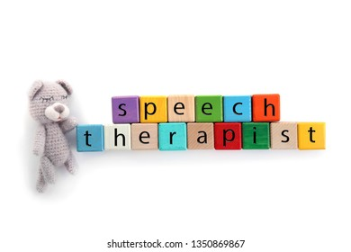 Cubes with text SPEECH THERAPIST and toy on white background