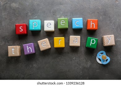 Cubes with text SPEECH THERAPY on grey background