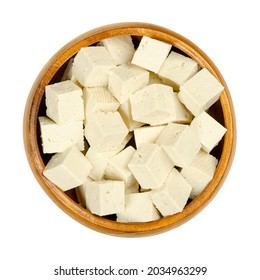 Cubes of white tofu, in a wooden bowl. Diced bean curd, coagulated soy milk, pressed into white blocks of different softness. A component of Asian cuisine, and a meat substitute. Close-up, from above.
