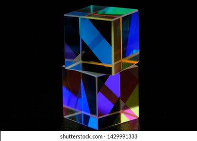 cubic glass prism refracting light rays on a dark background