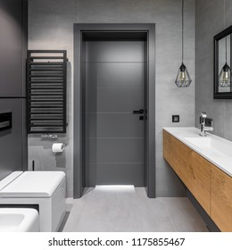 Cubic toilet and wooden cabinets in modern, gray bathroom