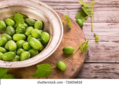 Cucamelons in plate  on rustic table with copy space