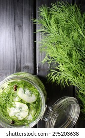 Cucumber and dill in vinegar. Mason jar and kitchen equipment.