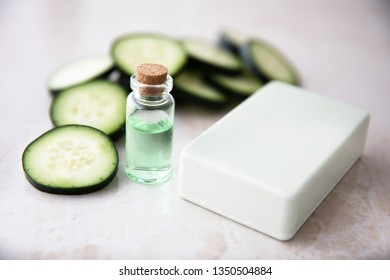 Cucumber extract in small bottle with bar of soap and cucumber slices.