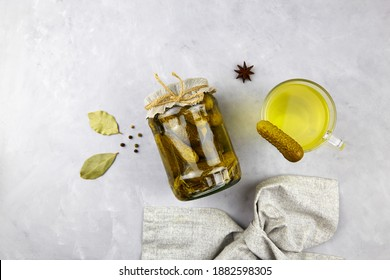 Cucumber pickle or pickle juice in glass, a jar with pickled gherkins on grey background,  top view. Trend drink, sports nutrition, healthy supplements.