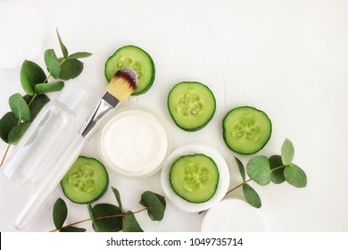 Cucumber slices, cosmetic cream jar and tonic mineral water in bottle, fresh green eucalyptus leaves, viewed above white background. Preparing Homemade Refreshing summer skincare