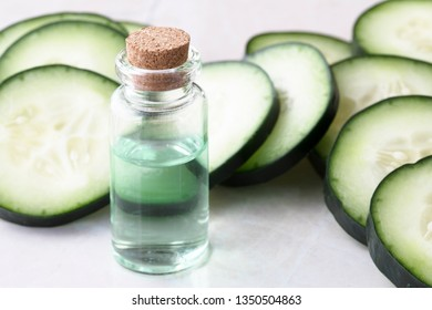 Cucumber slices and small bottle of cucumber extract.