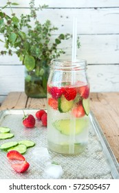 Cucumber and strawberry ice water on a wooden background