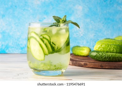 Cucumber water with mint leaves is popular detox drink Glass of antioxidant infusion with slices of vegetables on kitchen table and blue background