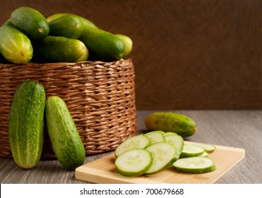 A lot of cucumbers in the basket. Cucumbers in a large wicker basket. Vegetables in wicker vessels for diet. A lot of cucumbers in a wicker box. Sliced cucumbers on a cutting board.