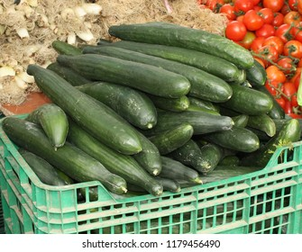 Cucumbers for sale in a crate in a open-air market stand in Spain.